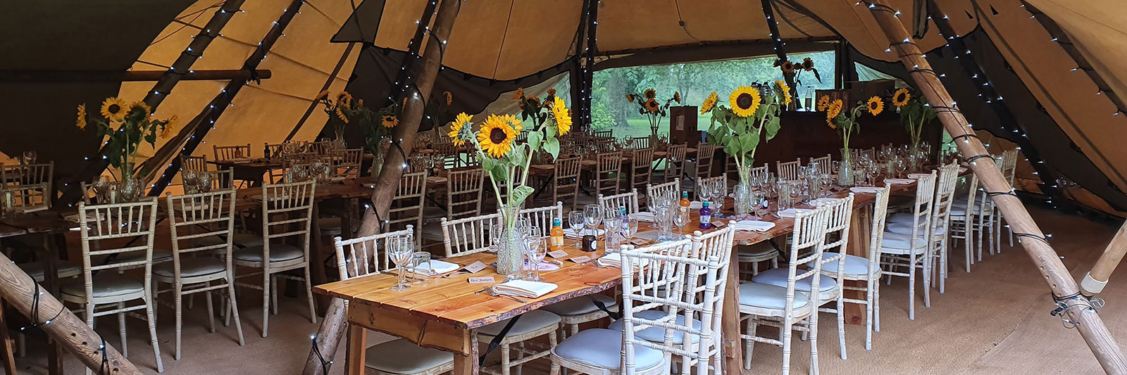 Tables dressed for a function with sunflowers in vases